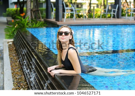 young woman relax in swimming pool, looking at camera wearing sunglassses and enjoy weather in tropical country on background of apartment building on sunny day with sunshine. Concept of enjoying life #1046527171