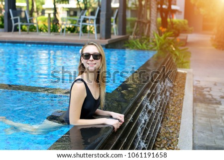 young woman relax in swimming pool, looking at camera wearing sunglassses and enjoy weather in tropical country on background of apartment building on sunny day with sunshine. Concept of enjoying life #1061191658