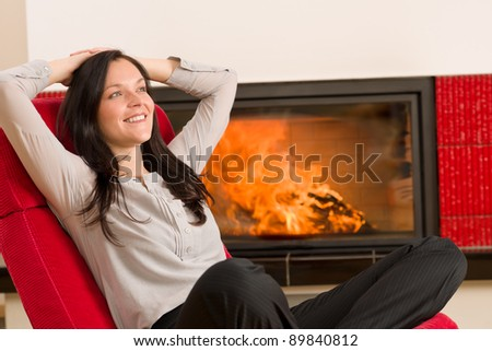 Young woman relax on red armchair by home fireplace