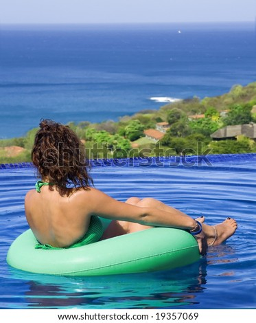 Young woman relaxes in a pool near the ocean