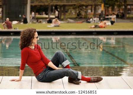young woman relaxes in the park, other relaxing people (out of focus) in the background #12416851