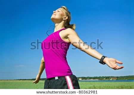 Young woman relaxing after running over blue sky, exercising and stretching outdoors, arms outstretched on summer sunny day.