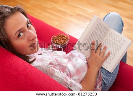 young woman relaxing and reading a book on a sofa