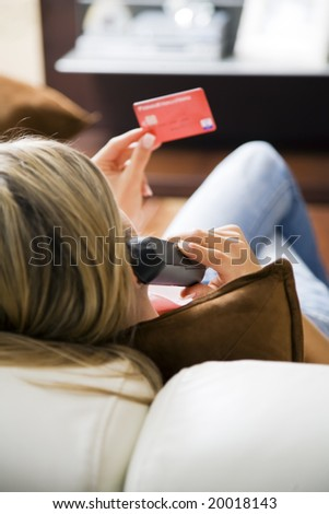 Young woman relaxing at home on the phone with credit card