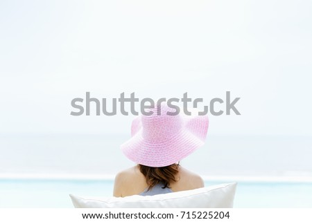 Young woman relaxing at swimming pool beside a beach in luxury Hotel during a vacation in summer and feeling happiness and relaxation. Relaxation concept.  #715225204
