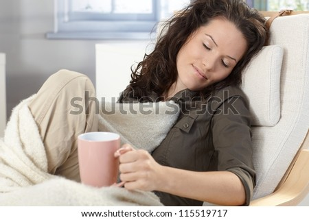 Young woman relaxing in armchair under blanket at home, holding tea mug, smiling, daydreaming.