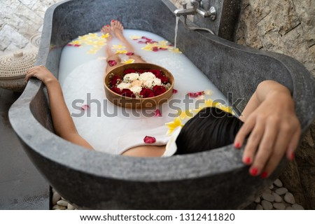 Young woman relaxing in black stone bath with tropical flowers and rose petals. Skin treatment, luxury spa concept.
