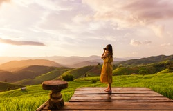 Young woman relaxing in green rice terraces on holiday at pabongpaing village, Mae-Jam Chiang mai, Thailand