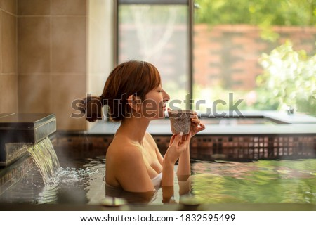 Young woman relaxing in hot spring and drinking tea