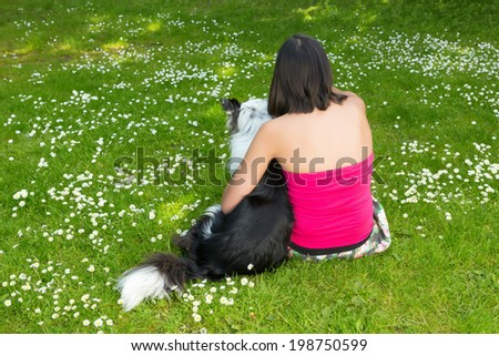 Young woman relaxing in the park with her border collie dog, with her back towards the camera