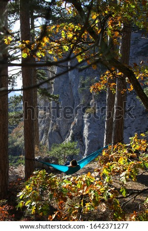 Young woman relaxing in the turquoise hammock in a mountains. Concept of relaxation and meditation. Fall season.