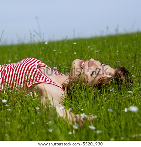 Young woman relaxing on a beautiful green meadow - stock photo
