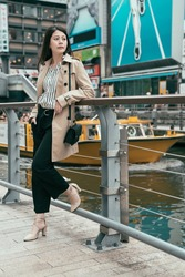 Young woman relaxing on bridge leaning on handrail after work waiting for friend. sightseeing tour boat on river in background with nippon runner billboard. beautiful lady enjoy city view with lake.