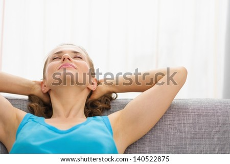 Young woman relaxing on couch in living room