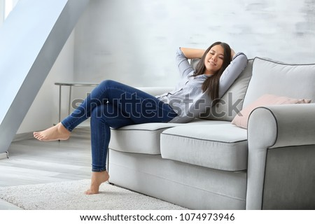 Young woman relaxing on cozy sofa in light room