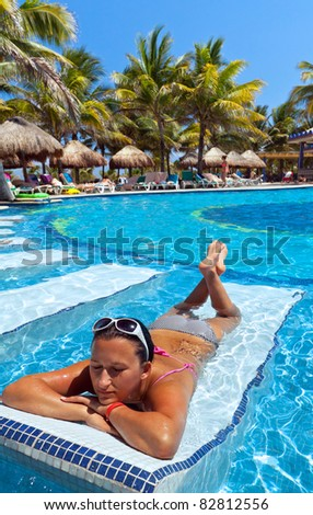 Young woman relaxing on swimming pool sunbed