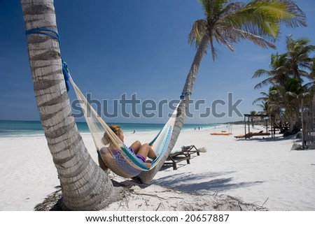 Young woman relaxing on the hammock on a tropical beach