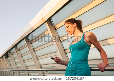 Young woman relaxing outdoors on a modern bridge while listening to music. #157234157