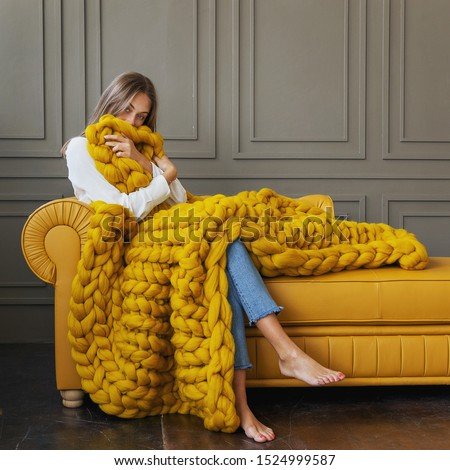 Young woman relaxing with chunky merino wool blanket. Relax, comfort lifestyle. Winter style. Сток-фото ©