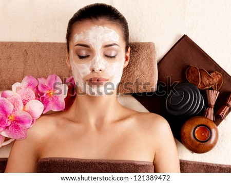 Young woman relaxing with cosmetic mask on face at beauty salon- indoors