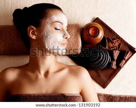 Young woman relaxing with facial mask on face at beauty salon- indoors