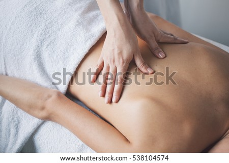 Photo of Young woman relaxing with hand massage at beauty spa.