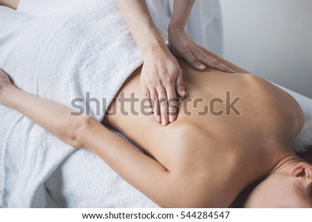 Young woman relaxing with hand massage at beauty spa.