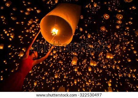 Young woman release sky lanterns to worship buddha\'s relics in yi peng festival, Chiangmai thailand