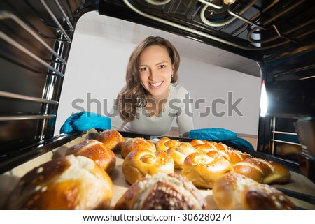 Young Woman Removing Bun Tray View From Inside Microwave Oven