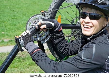 Young woman repairing bicycle during bike trip