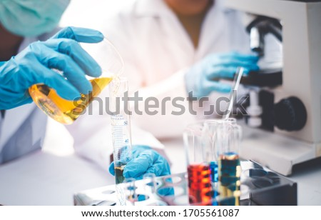 Young woman researcher doing experiment equipment and science experiments oil pouring scientist with test tube yellow making research in laboratory. Zdjęcia stock ©