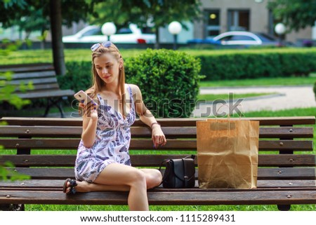 Young woman rest after shopping sitting on bench in park, use a mobile phone, paper bag next to it.