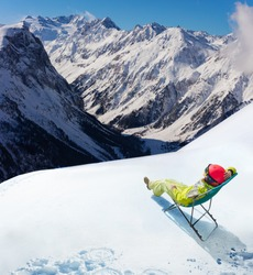 Young woman rest in cafe the deck chair on top of the mountain and Alpine peaks