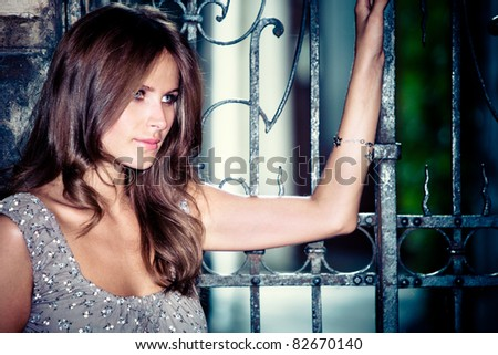 young woman rest upon a wrought iron entrance gate