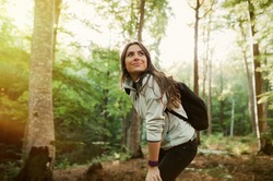 Young woman resting after a walk in the forest, carrying a backpack in the forest on sunset light in the autumn season.