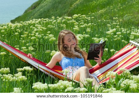 Young woman resting in a hammock and reading a book