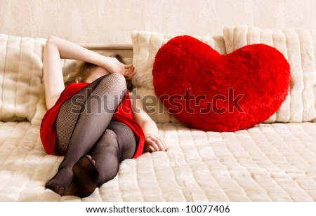 Young Woman Resting On A Bed And Heart Shaped Pillow. Concept ...