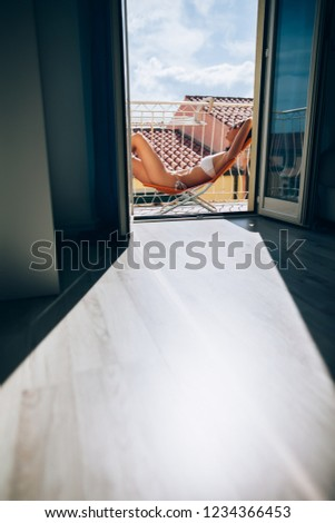Young woman resting on sun chair and sunbathing on hotel terrace on city roofs background. Vacation and summertime concept #1234366453
