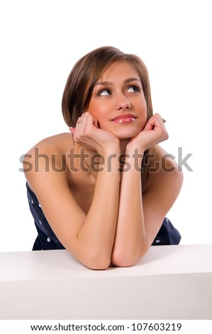 young woman rests her elbows on the white cube. White background