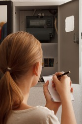 Young woman rewrites the electrical meter readings at home in Russia