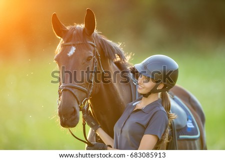 Young woman rider with her horse in evening sunset light. Outdoor photography in lifestyle mood