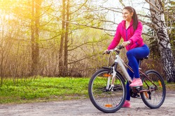 Young woman rides a bike along a path in the forest at sunset of a summer day