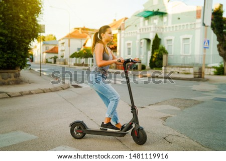 Young woman rides electric kick scooter on the street waiting on the crossroad wearing jeans in summer day evening traffic transport #1481119916