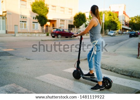 Young woman rides electric kick scooter on the street waiting on the crossroad wearing jeans in summer day evening traffic transport #1481119922