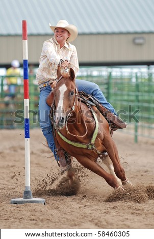 Young woman riding a horse in a pole bending race at a rodeo.