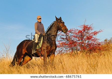 Young woman riding  a horse in autumn filed