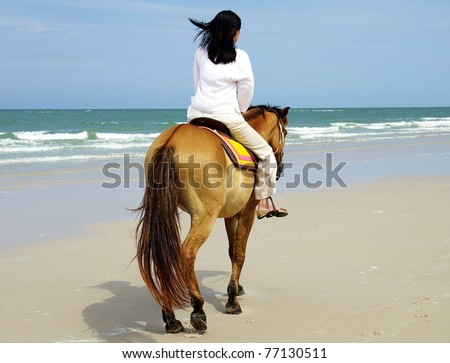 young woman riding a horse on the beach