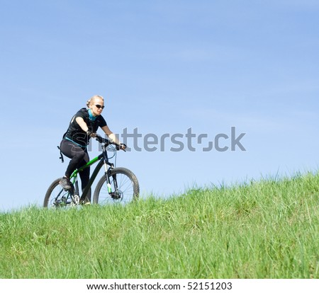 Young woman riding a mountain bike over blue sky