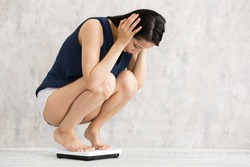 Young woman riding a weight scale.