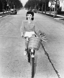 Young woman riding her bicycle with basket full of flowers and carrots